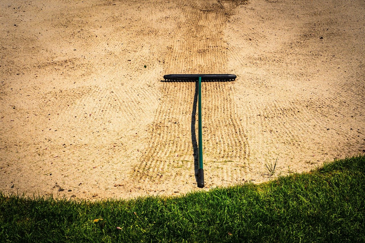 A golf course bunker with a rake in it